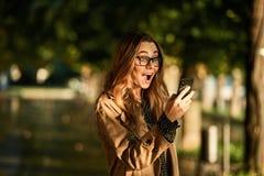 Retrato da mulher europeia que usa o telefone celular ao andar através da aleia vazia fotos de stock royalty free