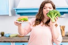 retrato da mulher excesso de peso com hamburguer que morde brócolis frescos nas mãos na cozinha em casa saudável imagem de stock