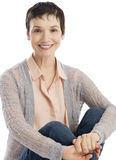 Retrato da mulher feliz que abraça joelhos fotografia de stock