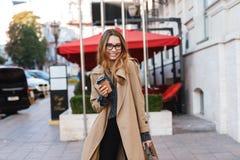 Retrato da mulher feliz que bebe o café afastado ao andar através da rua da cidade fotografia de stock