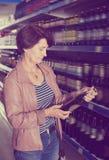 Retrato da mulher feliz que compra uma cerveja imagem de stock
