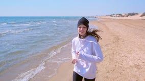 Retrato da mulher feliz que movimenta-se no treinamento corrido exterior do esporte da praia da areia do mar filme