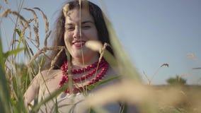 Retrato da mulher gorda despreocupada na colar do vestido do verão que olha a câmera através das orelhas do sorriso do trigo filme
