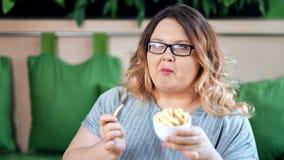 Retrato da mulher gorda feliz que come as batatas fritas apetitosas que levantam olhando a câmera video estoque