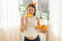 Retrato da mulher gravida de sorriso bonita nova com laranjas Alimento saudável, vitaminas naturais imagem de stock royalty free