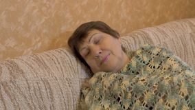 Retrato da mulher idosa feliz Está descansando no sofá vídeos de arquivo