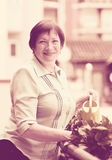 Retrato da mulher idosa que molha plantas domésticas Fotos de Stock Royalty Free