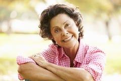 Retrato da mulher latino-americano superior que senta-se no parque fotos de stock royalty free