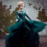 Retrato da mulher loura atrativa nova em um vestido verde bonito Fundo Textured, interior Penteado luxuoso fotografia de stock royalty free