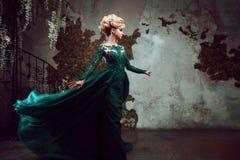 Retrato da mulher loura atrativa nova em um vestido verde bonito Fundo Textured, interior Penteado luxuoso imagens de stock