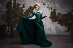 Retrato da mulher loura atrativa nova em um vestido verde bonito Fundo Textured, interior Penteado luxuoso imagem de stock royalty free