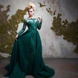 Retrato da mulher loura atrativa nova em um vestido verde bonito Fundo Textured, interior Penteado luxuoso Imagem de Stock