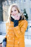 Retrato da mulher loura atrativa nova no inverno na câmera de sorriso do lenço do revestimento & de vista feliz amarela exterior Fotos de Stock