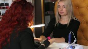 Retrato da mulher loura bonita no procedimento do tratamento de mãos no salão de beleza luxuoso video estoque