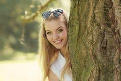 Retrato da mulher loura bonita que esconde atrás da árvore Fotografia de Stock