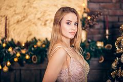 Retrato da mulher loura luxuoso no vestido de nivelamento dourado na árvore de Natal e nas velas do fundo Sorrisos bonitos 'sexy' imagem de stock royalty free