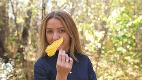 Retrato da mulher loura nova bonita e bonita feliz na floresta em cores da queda movimento 4k lento video estoque
