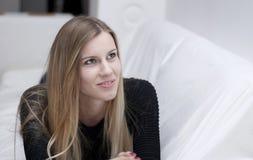 Retrato da mulher loura nova que descansa no sofá fotografia de stock