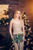 Retrato da mulher loura que veste a caixa de presente dourada da terra arrendada do vestido no fundo de decorações do Natal Feria fotografia de stock