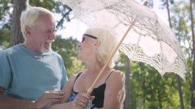 Retrato da mulher madura de sorriso positiva nos óculos de sol que estão fora sob o parasol branco Reunião do homem superior video estoque