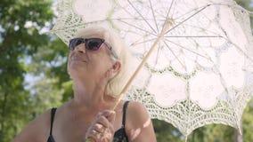 Retrato da mulher madura de sorriso positiva nos óculos de sol que estão no parque sob o guarda-chuva branco que olha ao redor vídeos de arquivo