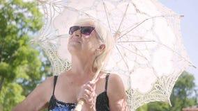 Retrato da mulher madura de sorriso positiva nos óculos de sol que estão no parque sob o parasol branco que olha ao redor e vídeos de arquivo