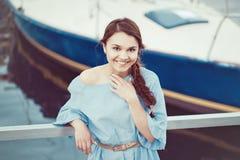 Retrato da mulher moreno caucasiano branca com pele bronzeada no vestido azul pelo litoral lakeshore com iate imagem de stock
