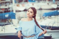 Retrato da mulher moreno caucasiano branca com pele bronzeada no vestido azul pelo litoral lakeshore com iate fotos de stock