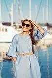 Retrato da mulher moreno caucasiano branca de sorriso com pele bronzeada no chapéu de vestido azul, pelo litoral lakeshore imagem de stock royalty free