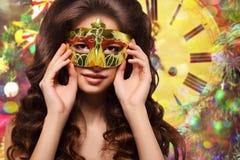 Retrato da mulher moreno nova em uma máscara do ouro em um fundo do ouro Fotografia de Stock