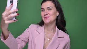 Retrato da mulher moreno nova no revestimento cor-de-rosa que fala com o amigo no videochat no smartphone no fundo verde filme