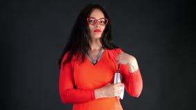 Retrato da mulher moreno 'sexy' com bordos vermelhos, no vestido vermelho, e espetáculos vermelhos, com a bolsa pequena branca, e video estoque