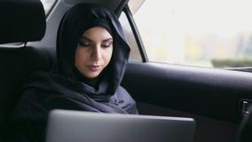 Retrato da mulher muçulmana atrativa nova no hijab que senta-se no banco traseiro no táxi e que usa seu portátil Slowmotion filme