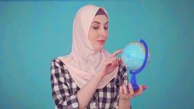 Retrato da mulher muçulmana bonita nova com vista do modelo do globo video estoque