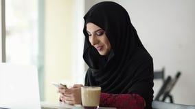 Retrato da mulher muçulmana de sorriso atrativa nova no hijab que senta-se no café e que datilografa uma mensagem em seu telefone filme