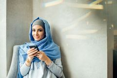 Retrato da mulher muçulmana feliz que usa o telefone celular ao sentar-se em um sofá Fotografia de Stock Royalty Free
