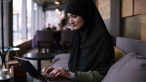 Retrato da mulher mu?ulmana nova de sorriso que trabalha no port?til moderno no caf? A mulher atrativa no hijab abre o portátil e filme