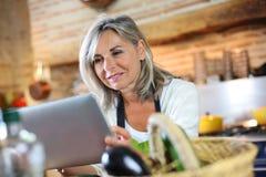 Retrato da mulher na cozinha que verifica a receita no Internet Fotos de Stock Royalty Free