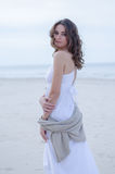 Retrato da mulher na praia Menina encaracolado-de cabelo bonita feliz completo, o cabelo de vibração do vento Retrato da mola na  fotos de stock royalty free