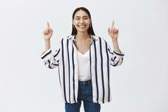 Retrato da mulher natural e à moda bonita nas calças de brim e blusa listrada, mãos de levantamento e apontar acima com índice imagem de stock
