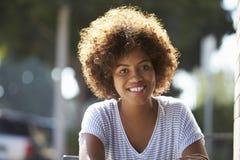Retrato da mulher negra nova feliz que senta-se fora imagens de stock royalty free