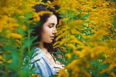 Retrato da mulher no perfil entre flores amarelas Fotos de Stock Royalty Free