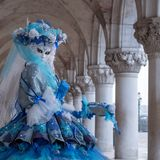 Retrato da mulher no traje, no chapéu e na máscara azuis bonitos sob os arcos nos doges palácio, Veneza, durante o carnaval Fotografia de Stock