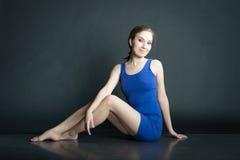 Retrato da mulher no vestido curto azul que senta-se no assoalho no fundo escuro fotografia de stock
