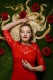 Retrato da mulher no vestido vermelho que coloca na grama com rosas fotografia de stock royalty free