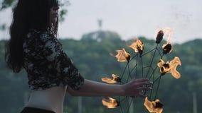 Retrato da mulher nova da benevolência na máscara que executa uma mostra com a posição da chama no riverbank na frente das árvore vídeos de arquivo