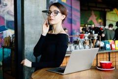 Retrato da mulher nova bonita do freelancer na cafetaria Senhora bonita com o telefone esperto em suas mãos usando o portátil e o imagem de stock royalty free