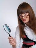 Retrato da mulher nova com um magnifier Fotografia de Stock Royalty Free