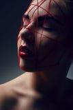 Retrato da mulher nova com Web vermelho na face fotos de stock royalty free