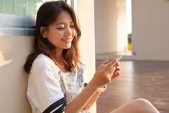 Retrato da mulher nova e adolescente bonita que olha ao pho móvel Fotos de Stock Royalty Free